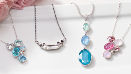 Four colorful Touchstone Crystal Necklaces on a white plate