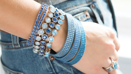 Closeup of Woman with hand in her jeans pocket wearing blue Touchstone Crystal bracelets
